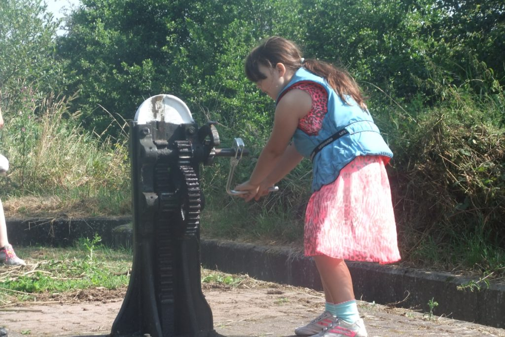 child in a lifejacket opening the lock paddle on the montgomery canal