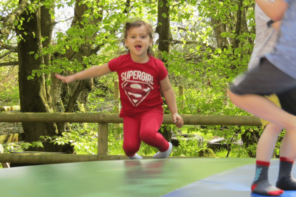 little girl in red supergirl t-shirt jumping on a plastic inflatable pillow