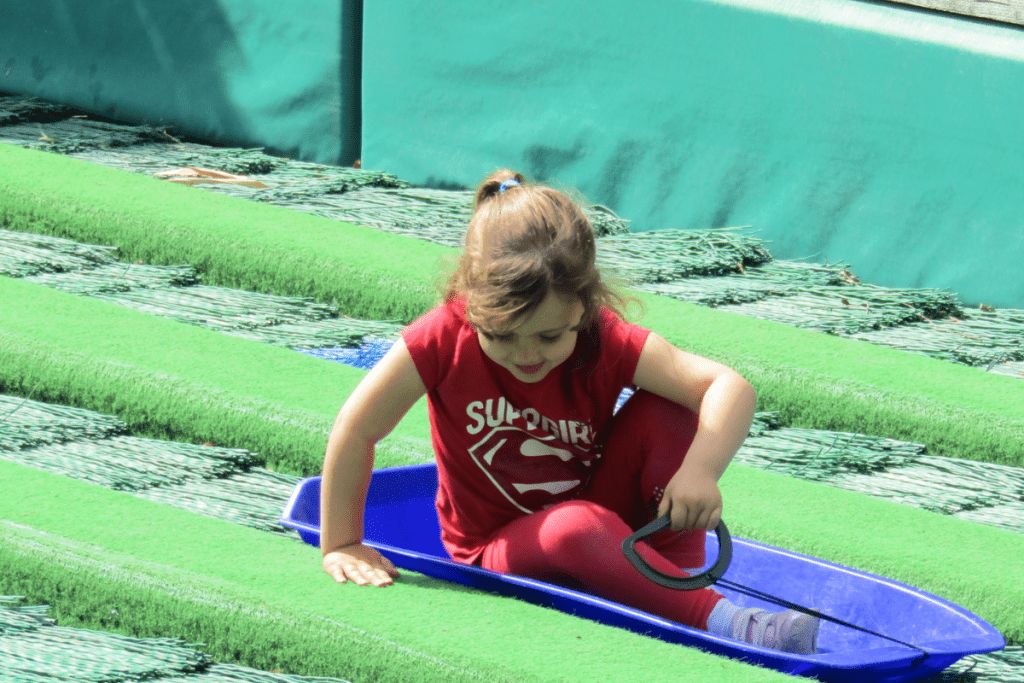 little girl getting of a blue sledge