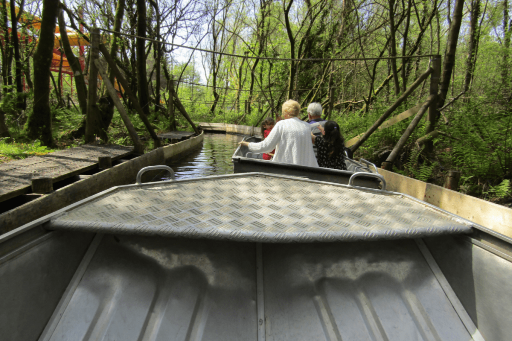metal boat with couple sitting in it and ropes overhead