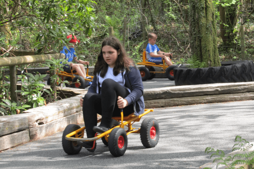 teenager peddling a four wheel kart with no steering wheel
