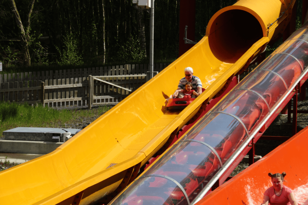 small dingy with a girl and a man coming down a yellow water slide