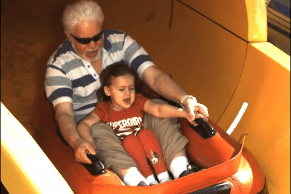 little girl and elderly man on a small dingy coming down a water slide
