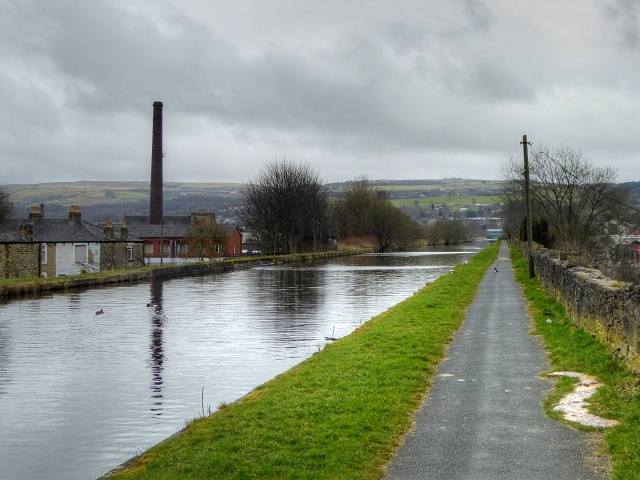 a picture showing a straight stretch of canal with houses to one size and the canal level with their roofs