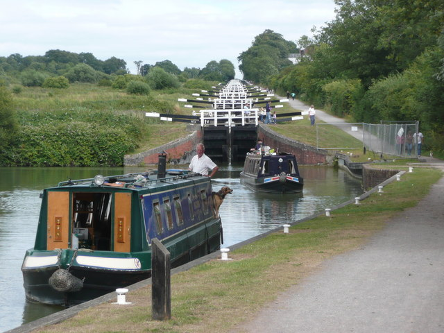 two narrowboats coming out of a lock with several locks visable going high in the sky behind them