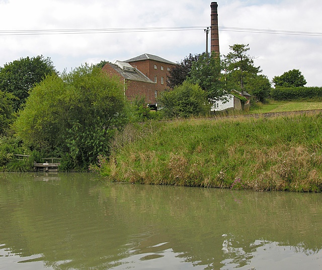 a picture of a tall chimney next to a builing behind the canal