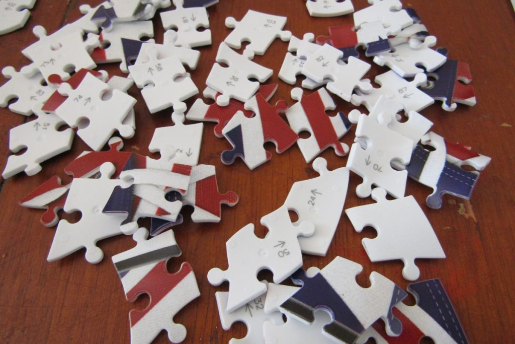 a selection of the jigsaw pieces showing either their design or their number ready to build the ravensburger 3d union jack sneaker puzzle