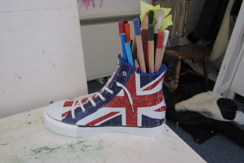 the completed ravensburger 3d union jack sneaker puzzle being used as a desk tidy with pens where the foot goes