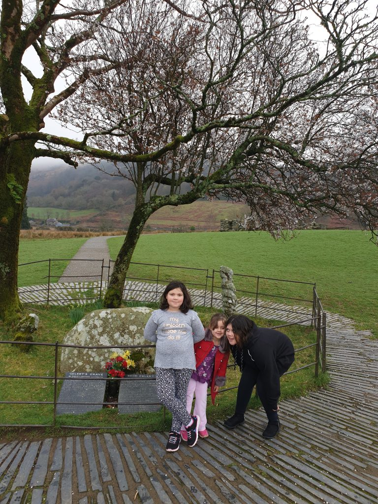 three girls by gelerts grave which is a big stone, two slate plaques with Gelerts stoy in welsh and english and a tree inside a fenced area