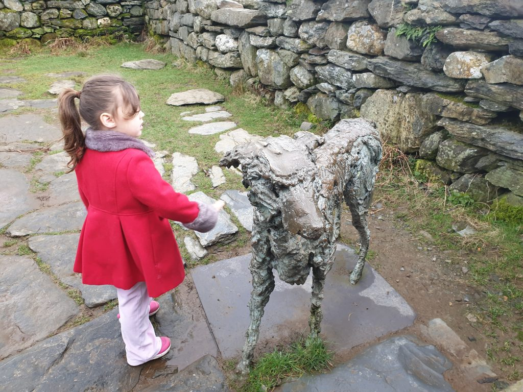 a silver statue of a dog to represent Gelert the faithful dog of Princce Llewelyn the great