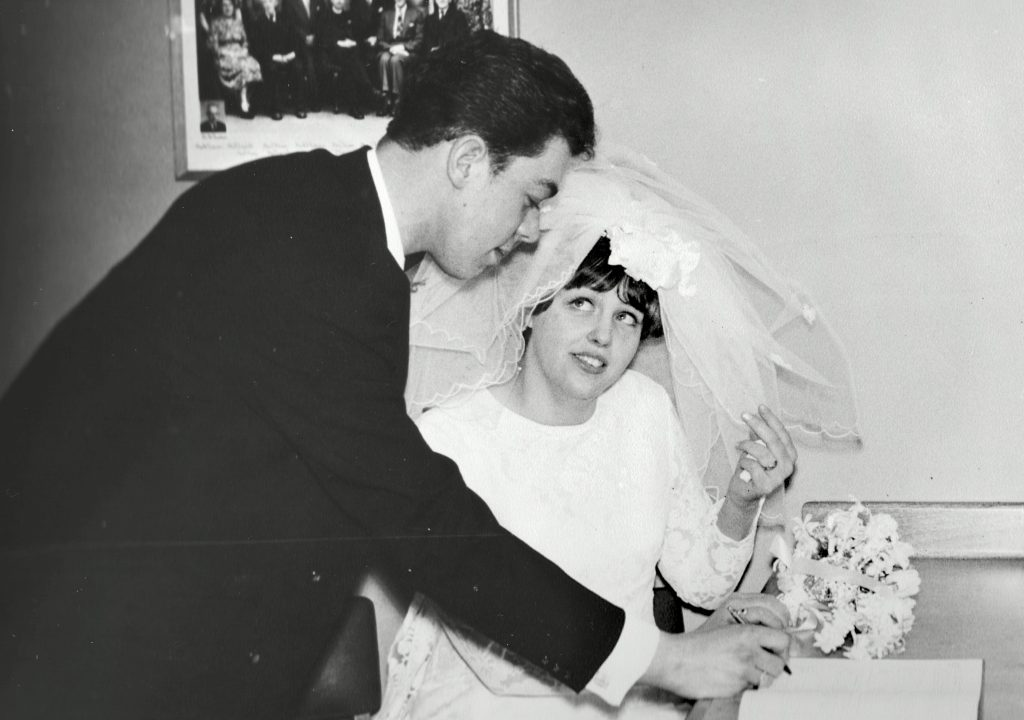 professional black and white wedding photograph of the bride and groom signing the register book in 1969