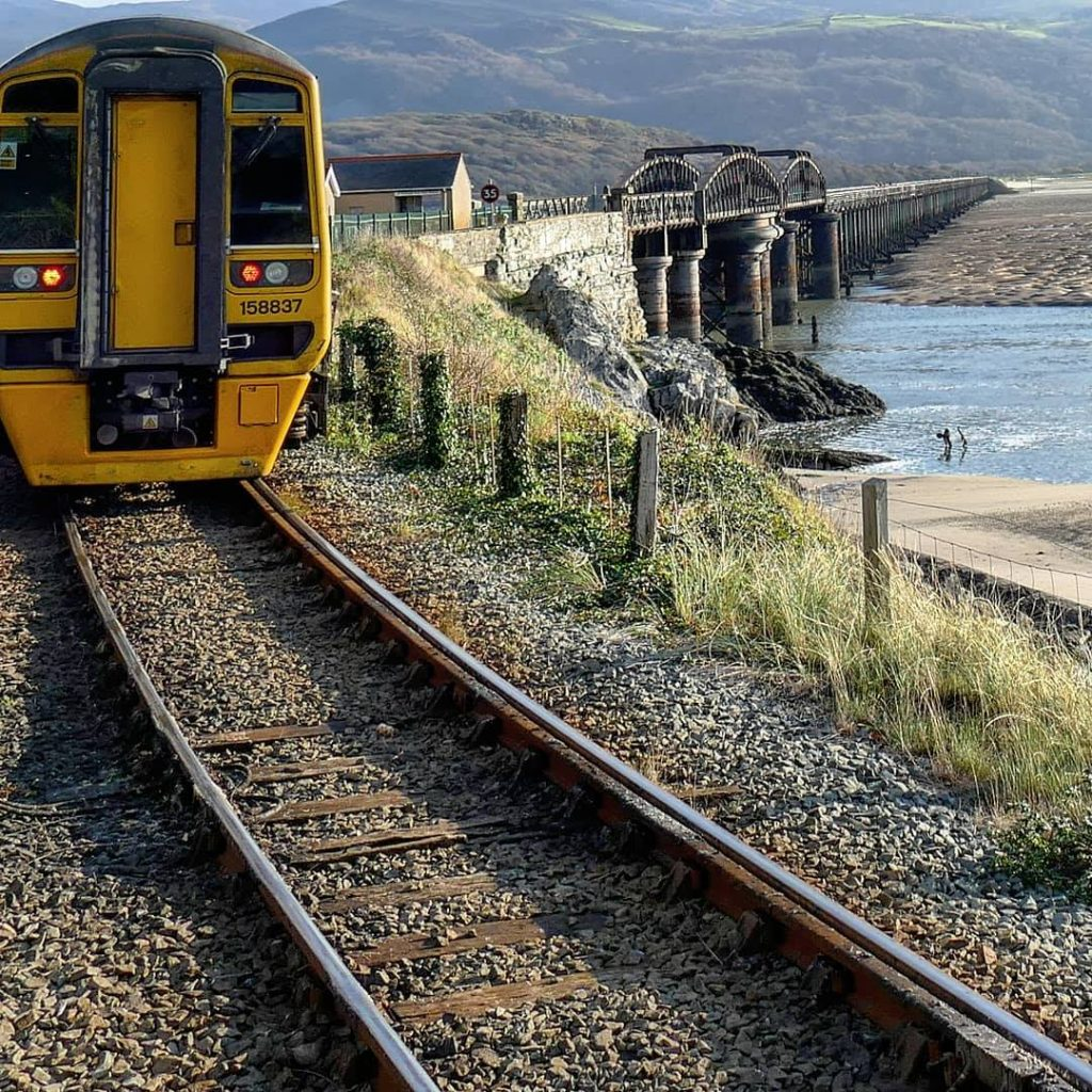 the rear of a train about to head on the wooden Barmouth viaduct over the river Mawddach on the Cambrian Coast railway