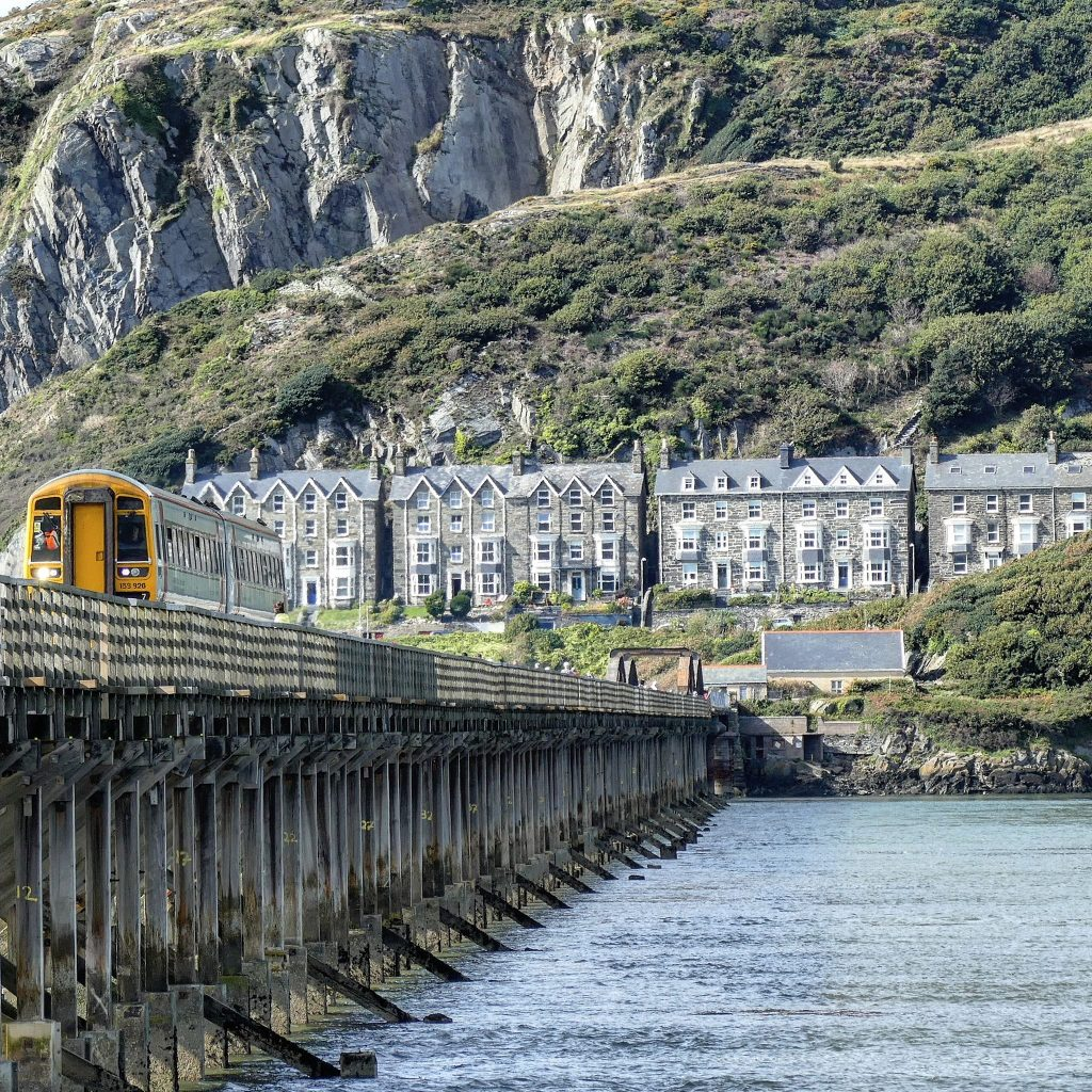 train on a wooden viaduct over the river Mawddach on the Cambrian Coast railway