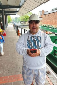 man wearing white hard hat stood beside a canal boat by the Dudley Tunnel