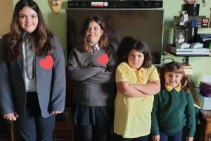 four girls stood in a line wearing their school uniforms