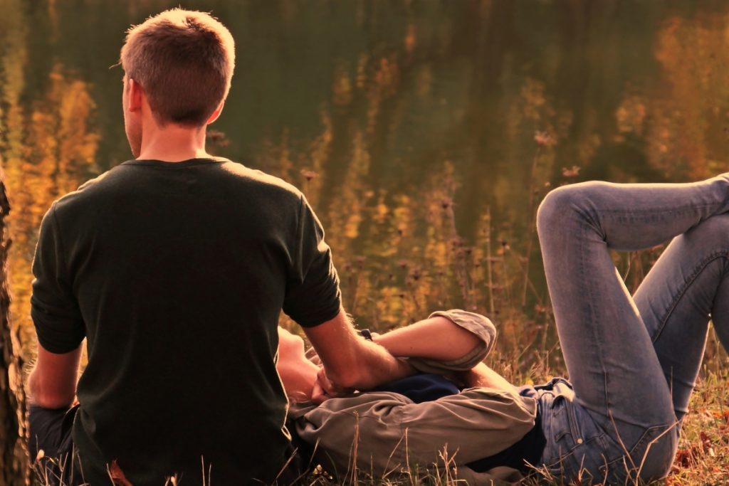couple snuggled together in an autumn meadow filled with the colours of autumn