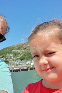 little girl with a waterfront back ground and mountain selfie