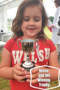 Small girl with brown hair and red t-shirt holding a winning silver cup
