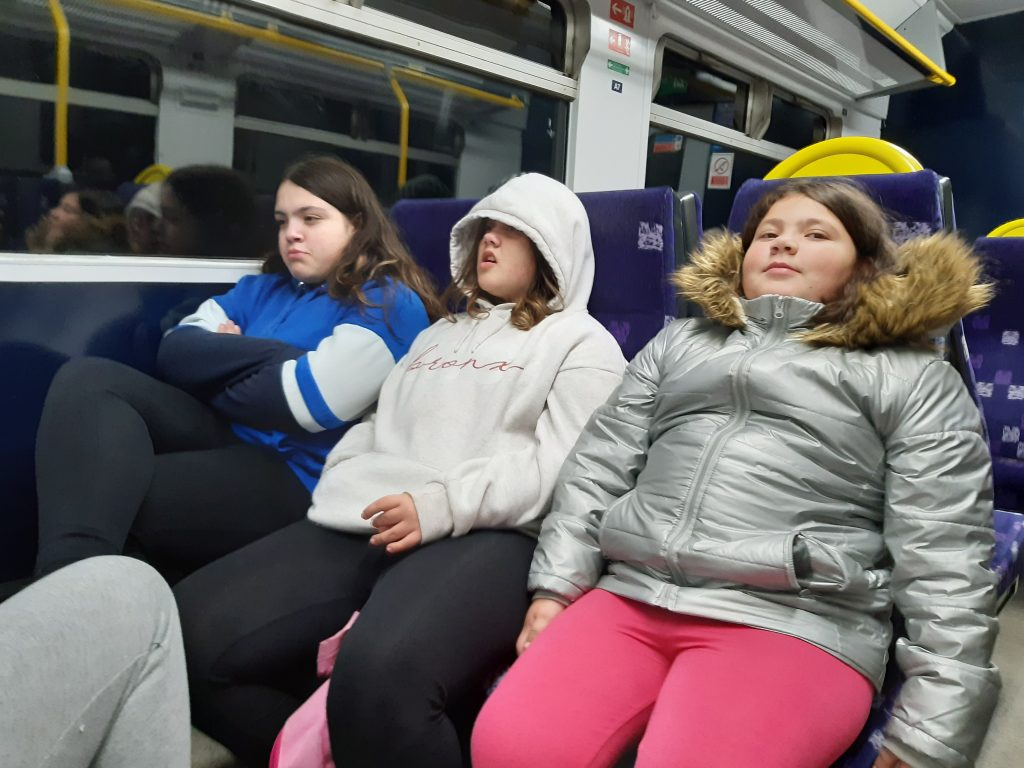 three sleepy girls asleep on a train