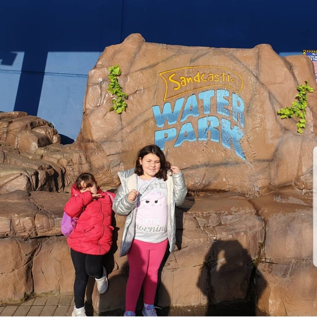 girls stood by a water feature saying sandcastle water park at blackpool