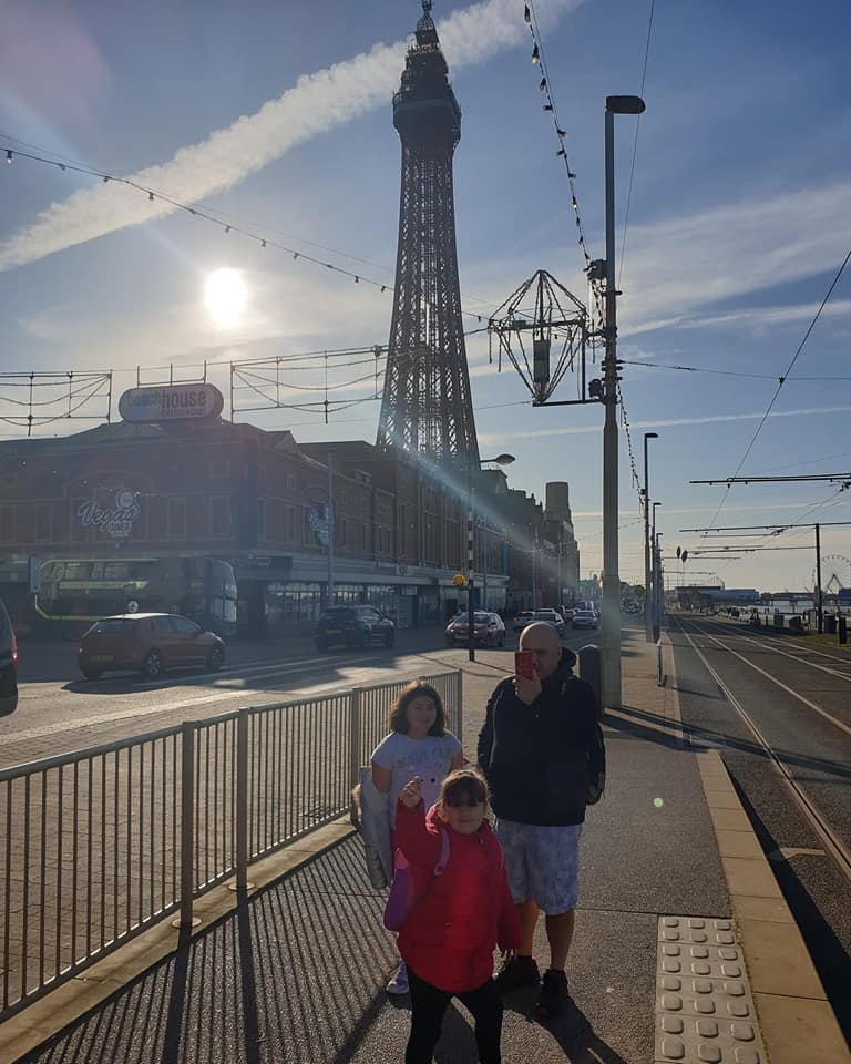 blackpool with tower in background and family waiting at tram stop