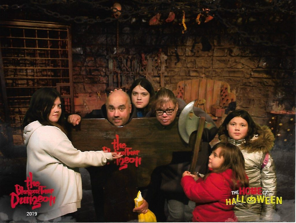 blackpool dungeon family photo of parents heads in stocks and children looking like they're about to chop their heads off