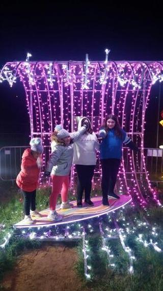 four girls at blackpool illuminations standing on a surfboard in front of lights looking like a wave