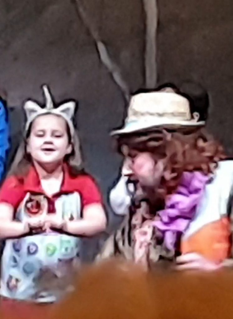 screenshot from a video of a little girl in a rainbow uniform on stage with a panto character
